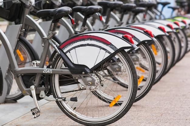 Fila de bicicletas bicicletas estacionadas vintage para alquilar en la acera.