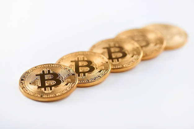 Fila de bitcoins de oro brillantes como la criptomoneda más grande del mundo aislada en el fondo blanco.