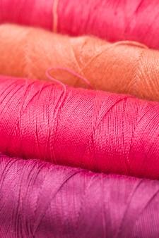 Fila de bobinas de hilo de colores cálidos