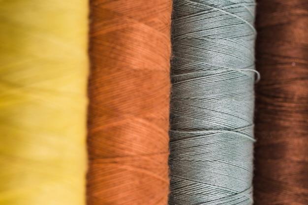 Fila de bobinas de hilo de diferentes colores