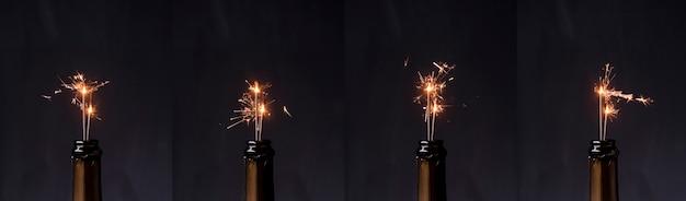 Fila de botella de champagne con bengala de fuego sobre fondo negro