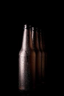 Fila de botellas negras de cerveza
