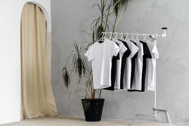 Fila de camisetas blancas y negras colgadas en una rejilla, cerrar