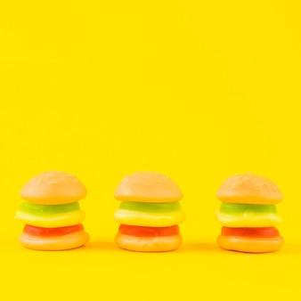 Fila de los caramelos coloridos de la hamburguesa en fondo amarillo