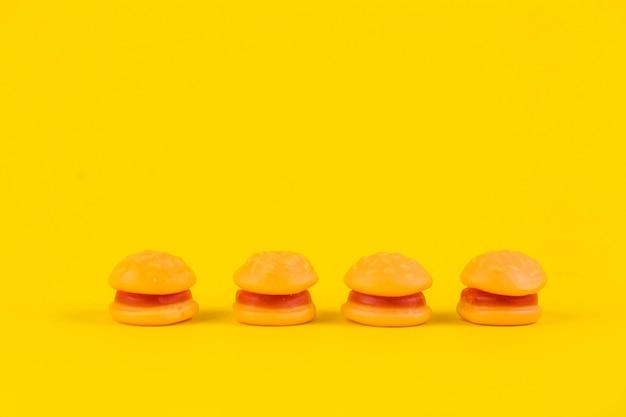 Fila de caramelos de hamburguesa sobre fondo amarillo