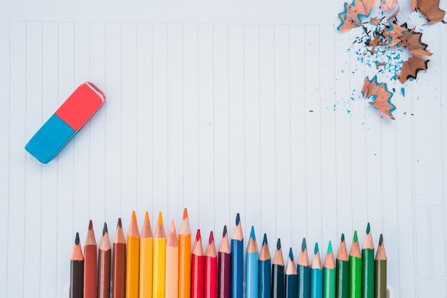 Fila de colores de lápiz con borrador y lápiz afeitado sobre papel blanco