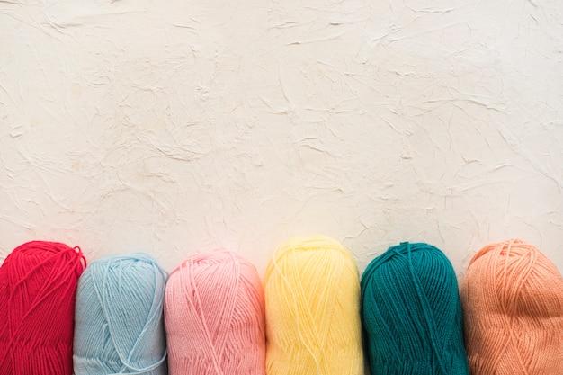 Fila de coloridas madejas de hilo
