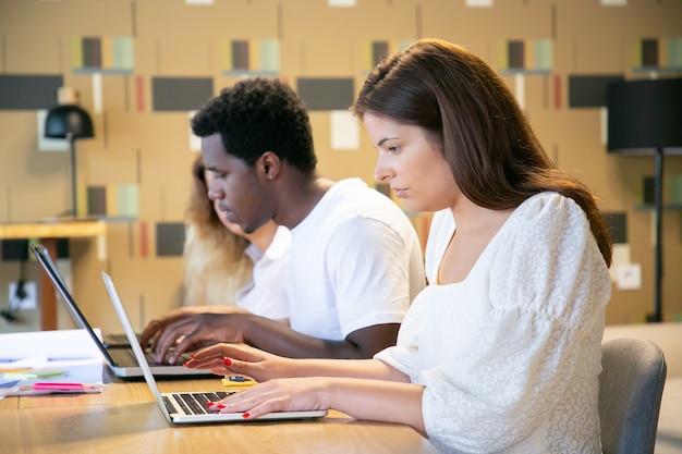 Fila de compañeros de trabajo centrados serios sentados a la mesa y escribiendo en portátiles