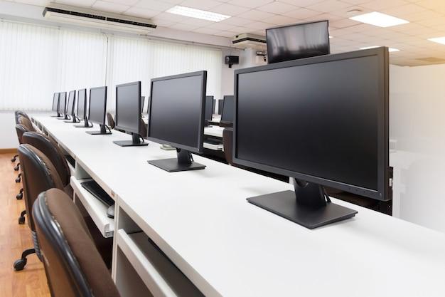 Fila de computadoras en los escritorios en el aula en el centro de capacitación general