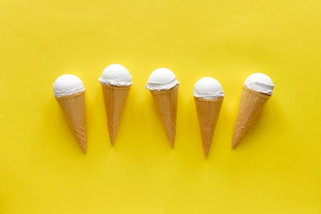Fila de conos cremosos de helado de vainilla en amarillo
