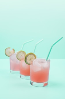 Fila de copas de cóctel con cubitos de hielo; pajita; rodajas de limón sobre fondo de menta