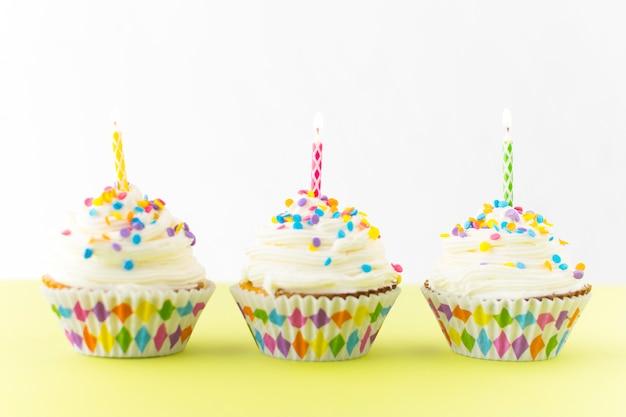 Fila de cupcakes frescos con velas de colores en superficie amarilla