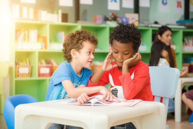 Fila de los estudiantes elementales multiétnicos que leen el libro en sala de clase. imágenes de estilo de efecto vintage.