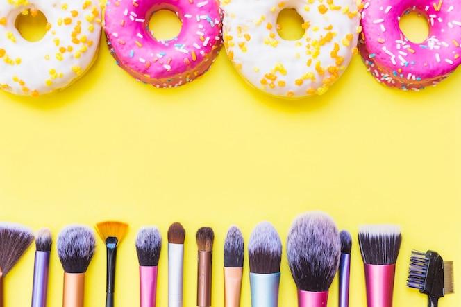 Fila de pinceles de maquillaje y donas sobre fondo amarillo