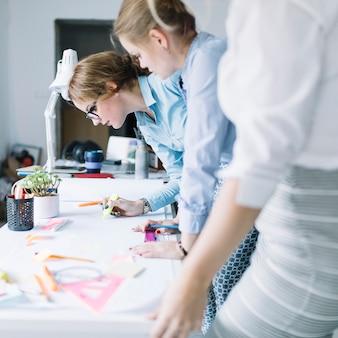 Fila de empresarias que dibujan proyecto en el libro blanco en el lugar de trabajo