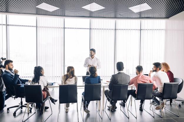 Fila de empresarios irreconocibles sentarse en la sala de conferencias en el evento empresarial.