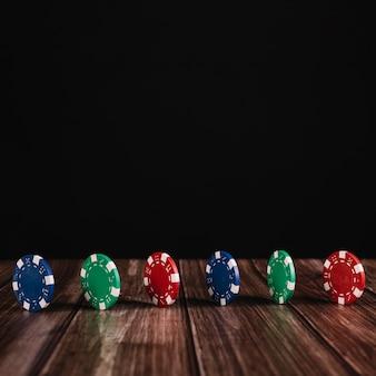 Fila de fichas de casino colorido en superficie de madera