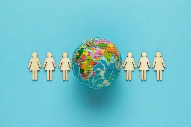Una fila de figuras humanas y un modelo del globo terráqueo sobre un fondo azul. día de la tierra. el concepto de protección del medio ambiente.