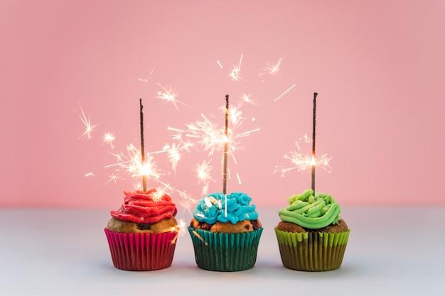 Fila de fuegos artificiales iluminados sobre los cupcakes contra fondo rosa