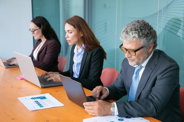 Fila de gente de negocios enfocada que trabaja en computadoras en una mesa con gráficos de papel