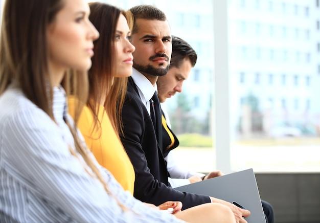 Fila de gente de negocios tomando notas en el seminario con especial atención a la sonriente joven