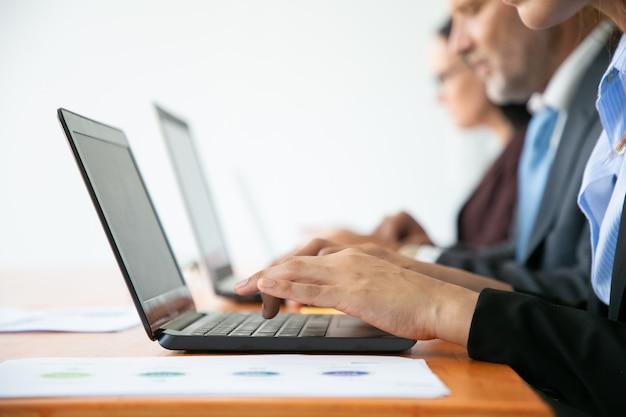 Fila de gente de negocios trabajando en computadoras. manos de empleados escribiendo en teclados de portátiles.