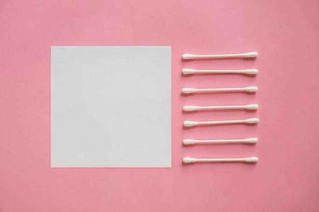 Fila de hisopos de algodón cerca de la nota adhesiva en blanco sobre fondo rosa