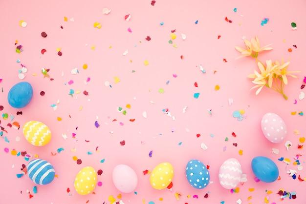 Fila de huevos de pascua entre confeti brillante