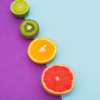 Fila inclinada de frutas cítricas y kiwi sobre fondo azul y púrpura doble