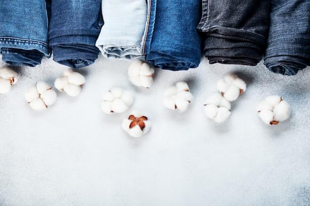Fila de jeans enrollados y flores de algodón