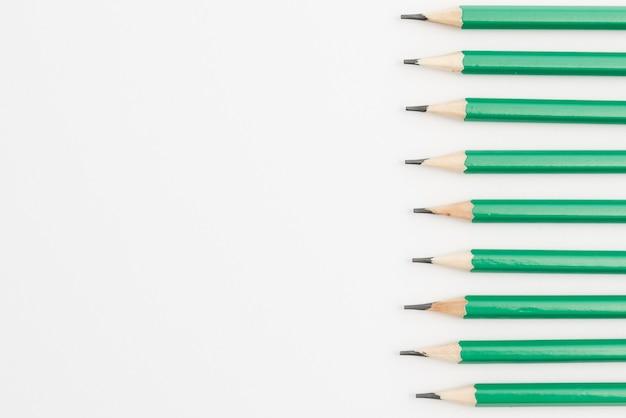 Fila de lápices afilados verdes sobre fondo blanco.