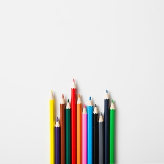 Fila de lápices de colores afilados contra el fondo blanco