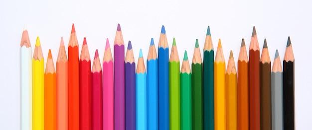 Fila de lápices de colores con onda sobre fondo blanco