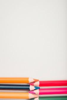Fila de lápices de colores en la parte inferior de la superficie blanca