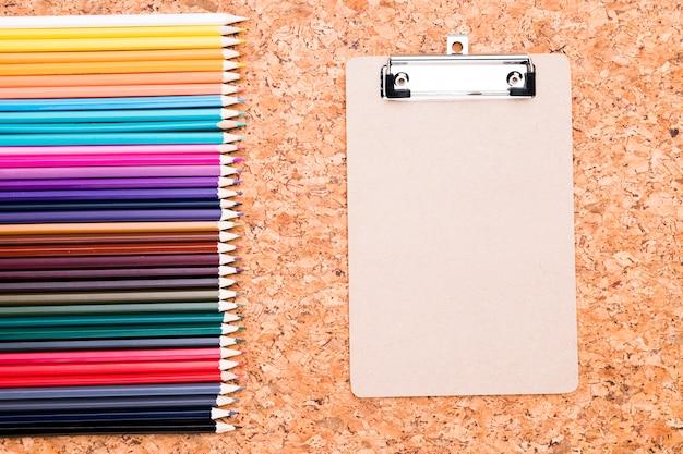 Fila de lápices de colores y portapapeles en el fondo de corcho por encima