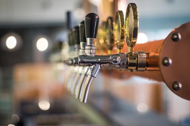 Fila de la lengüeta de la cerveza de barril en la cima de la barra contraria en la opinión del primer, época de la celebración.