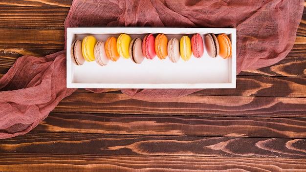Fila de macarrones en la caja de madera blanca sobre la mesa