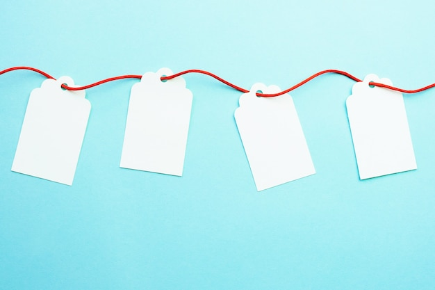 Fila de maquetas de etiquetas de regalo en blanco en una cadena de cinta roja sobre azul
