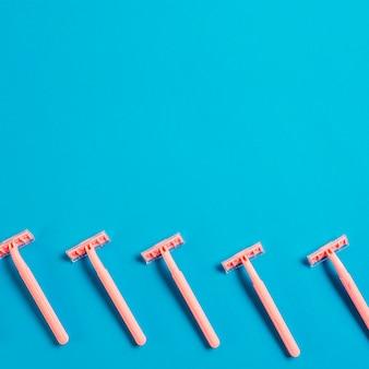 Fila de la maquinilla de afeitar sobre fondo azul