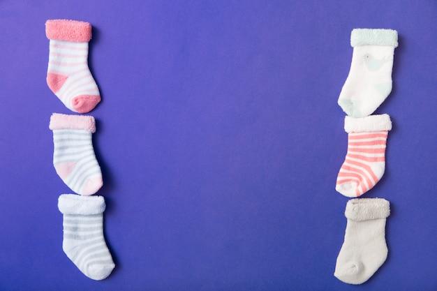 Fila de muchos calcetines de bebé sobre fondo azul