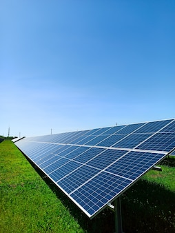 Una fila de paneles solares se encuentra en un campo verde, contra el cielo azul. un símbolo de energía limpia, preocupación por el medio ambiente, un concepto.