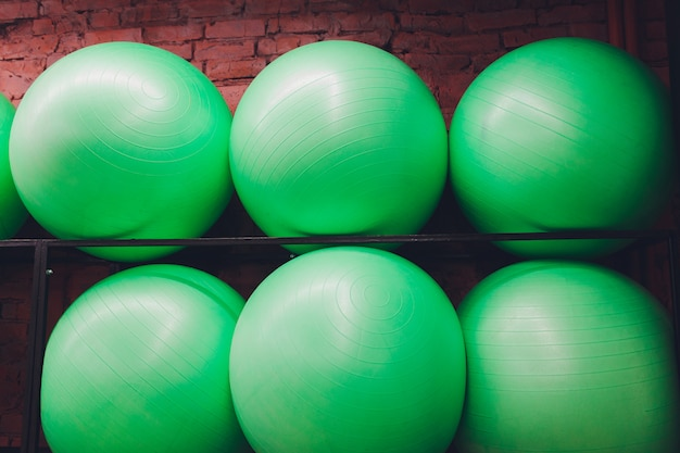 La fila de pesas que retrocede se alineó en un gimnasio esperando a los clientes con foco en la tercera y cuarta pesas de la fila.