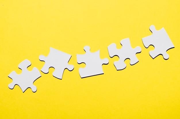 Fila de pieza del rompecabezas blanco sobre superficie amarilla