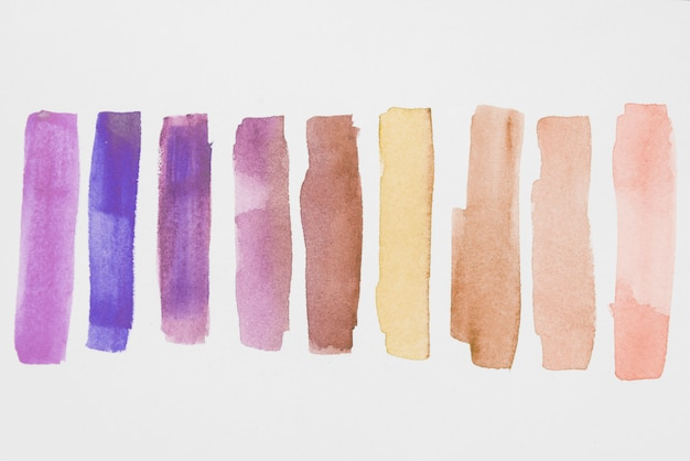 Fila de pinturas violetas y marrones sobre papel blanco