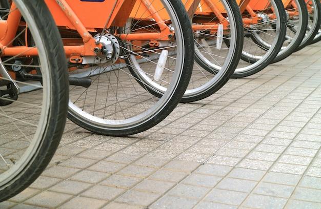 Fila de ruedas de bicicleta en la acera del centro