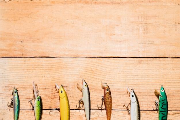 Fila de señuelos de pesca de colores en el escritorio de madera