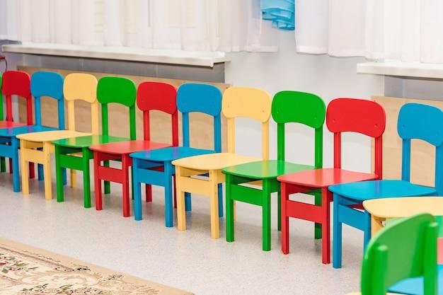 Una fila de sillas para niños multicolores vacías.