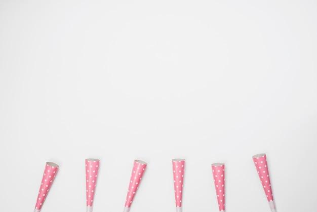 Fila de sopladores de cuerno de fiesta rosa sobre fondo blanco