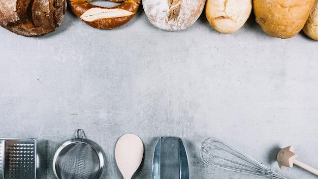 Fila superior de panes y equipos para hornear utensilios sobre fondo blanco grunge