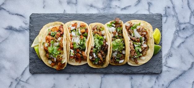 Fila de tacos callejeros mexicanos en pizarra con carne asada y al pastor en tortilla de maíz
